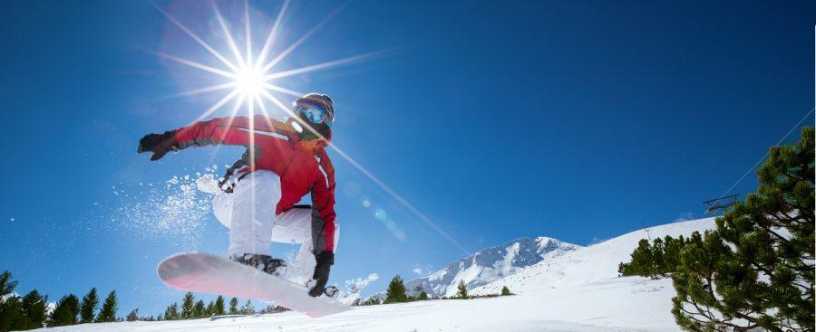 Snowboarder die in de zon aan het snowboarden is