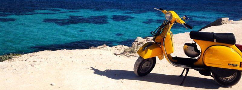 Gele scooter bij een zandstrand in Le Marche